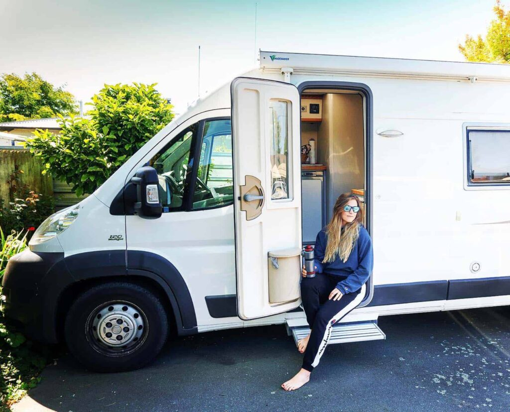 Woman holds water filtration bottle while sitting in an RV