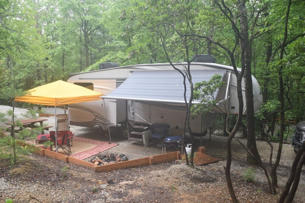 Fifth Wheel camper with orange pop up cover outside, rug surrounded by trees