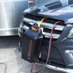 A CarGenerator backup power supply hangs from the grill of a vehicle.
