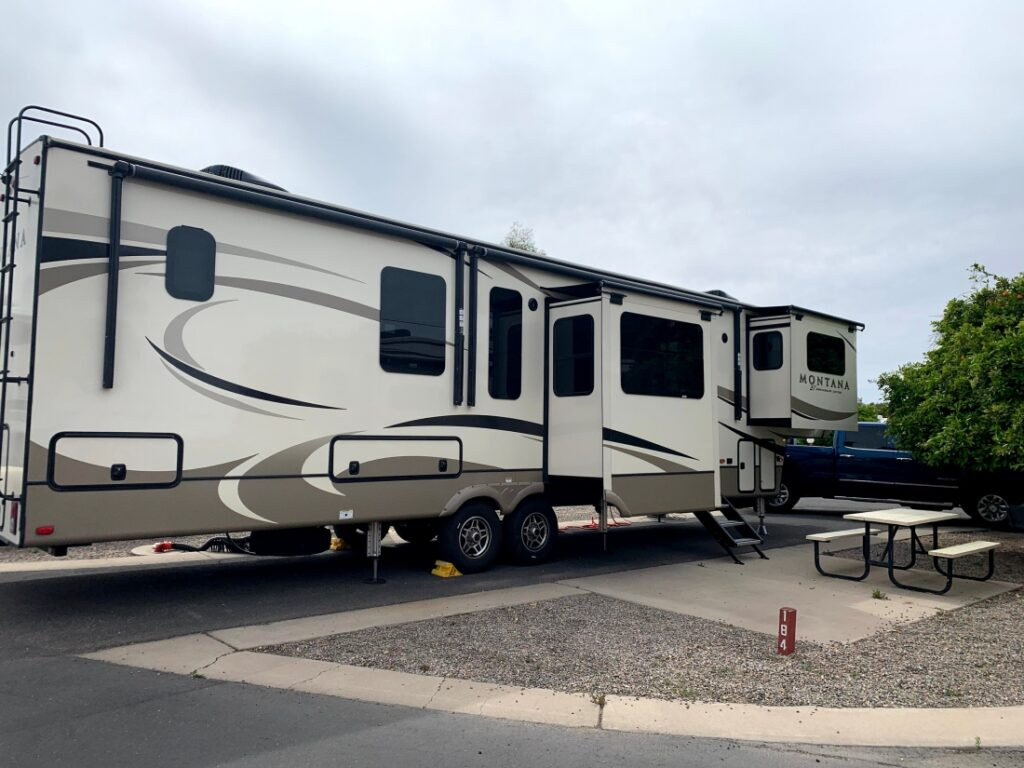 Fifth wheel RV parked on cement with slides out. Picnic table nearby.