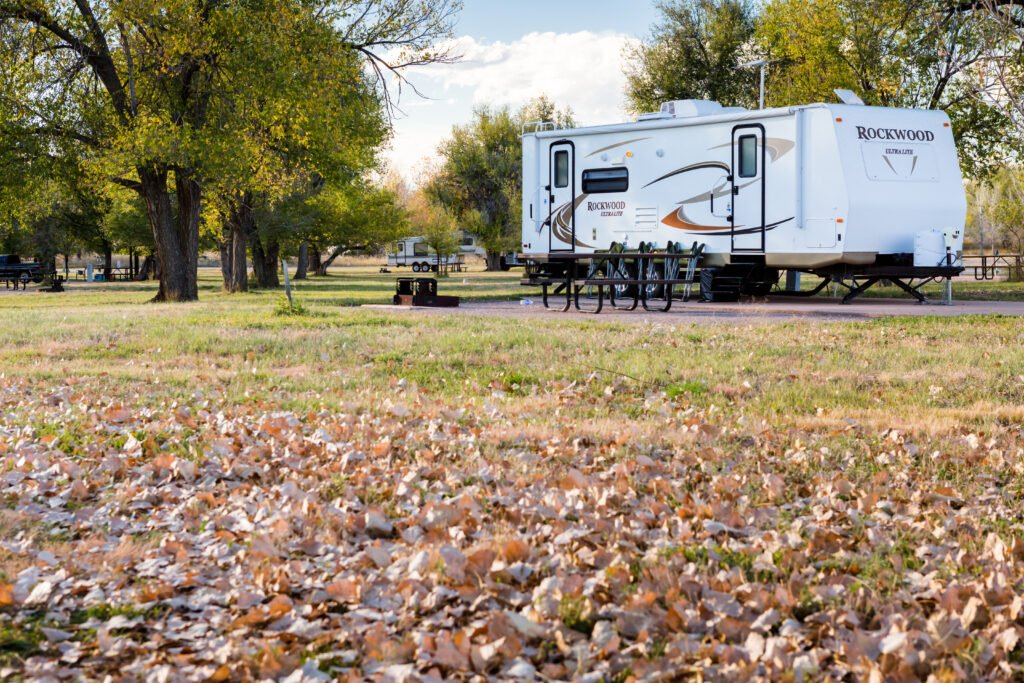 leaves with RV in background living in an RV full time in a park